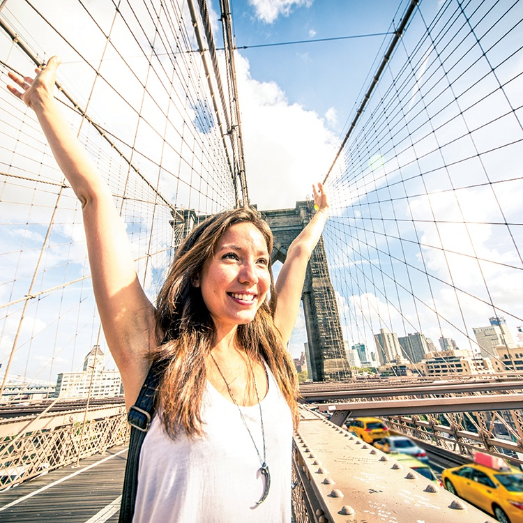 High school female student exploring New York City on Brooklyn Bridge