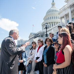 High school students speaking with a Congressman on the steps of the U.S. Capitol in Washington, DC