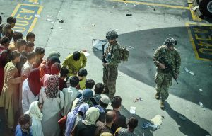 Walik Koshar/AFP/Getty Images - People waiting at Kabul airport to flee Afghanistan as U.S. soldiers stand guard.